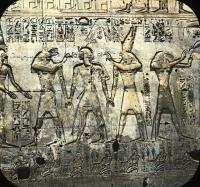 Боги Упуаут и Гор держат за руки фараона. За Гором стоит бог Тот