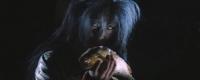 """Кайбё в образе человека ест рыбу. Кадр из фильма """"Призрачный замок"""""""